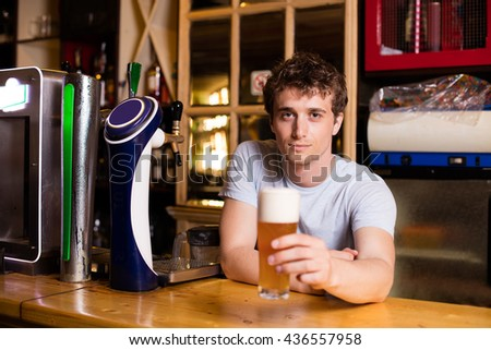 young bartender serving beer in a pub