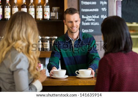Young bartender serving coffee to female friends at cafe - stock photo
