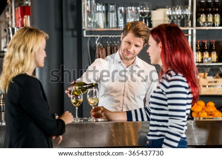 Young bartender serving wine to female customers at bar counter - stock photo