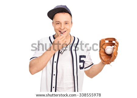 Young baseball coach holding a ball in a baseball glove and blowing a whistle isolated on white background - stock photo