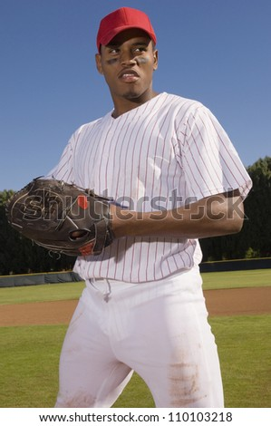 Young baseball pitcher standing on field and looking away - stock photo