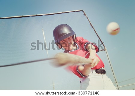 Young baseball player hitting the ball.  Vintage instagram effect, motion blur on bat and ball - stock photo