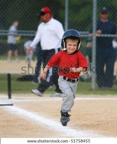 Young baseball player running and smiling during game - stock photo