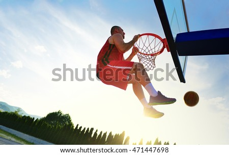 Young basketball player drives to the hoop for a high flying slam dunk in front of sunset sky