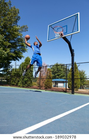 Young basketball player drives to the hoop with some fancy moves. - stock photo