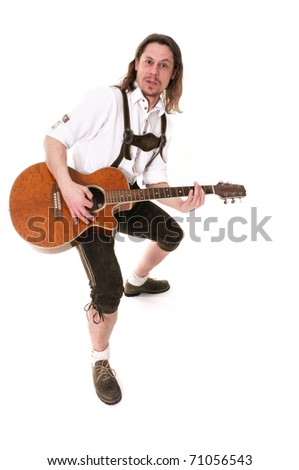 Young bavarian muscian in traditional costume playing guitar - stock photo