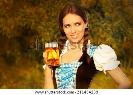 Young Bavarian Woman Holding Beer Tankard - Young woman in German dress holding a glass beer mug