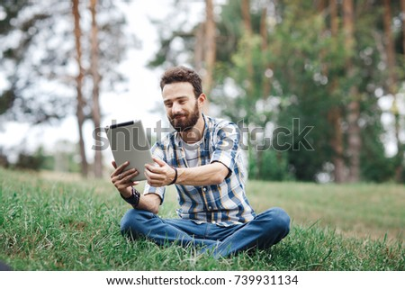 Young beard man using the tablet in the park siting on the grass