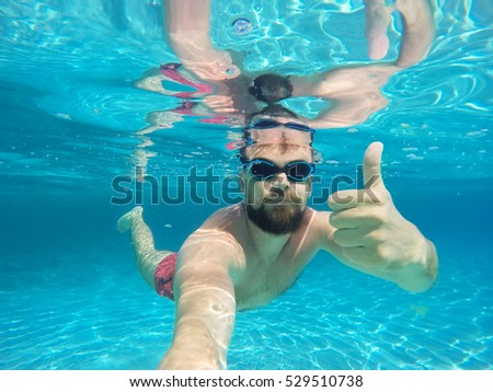 Young beard man with glasses diving in a blue clean water with thumb up