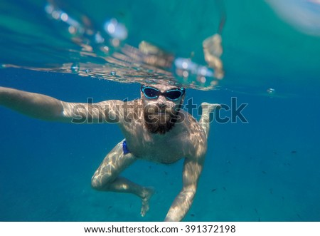 Young beard man with mask diving in a blue clean water