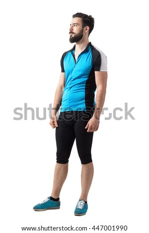 Young bearded bicyclist relaxing and looking up side view. Full body length portrait isolated over white studio background. - stock photo