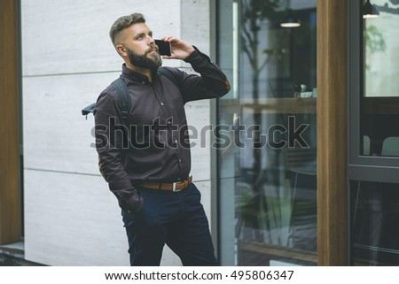 Young bearded businessman hipster,wearing brown shirt and dark blue trousers,standing outside and talking on cell phone.Guy with the backpack using the gadget. In the background is a modern building.