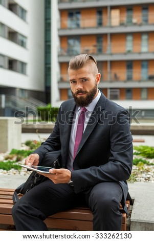 Young bearded businessman sitting on a bench and using tablet pc. Outdoor photo