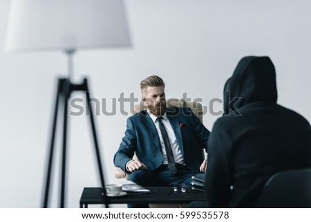 Young bearded businessman talking with anonymous person in black hood isolated on grey