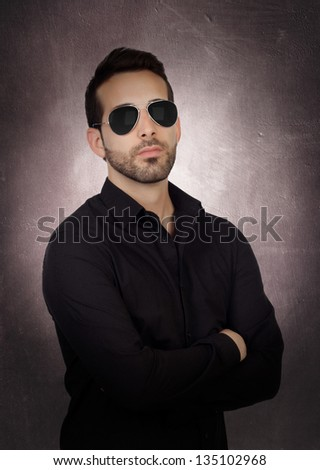 Young bearded businessman with sunglasses on a over gray and irregular background - stock photo