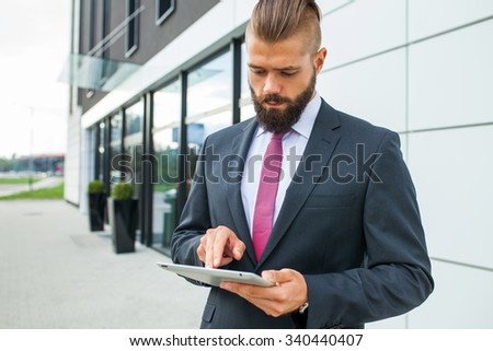 Young bearded businessman writting business e-mail using his tablet pc. Outdoor photo