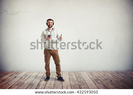 Young bearded Caucasian man in casual clothes with headphones and phone is showing a thumb up gesture in empty room with white wall and wooden floor - stock photo