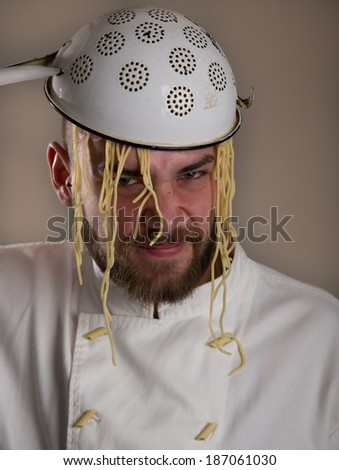 young bearded chef with pasta on his head