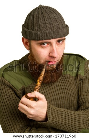 young bearded guy smoking a pipe on a light background