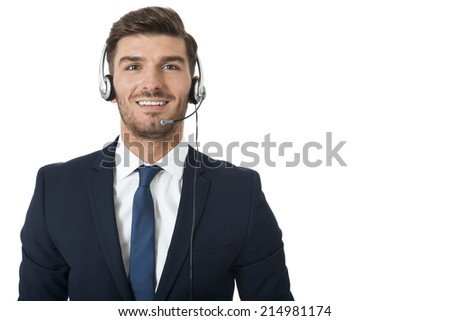 Young bearded handsome man wearing formal business suit and headset with stereo headphones and microphone while smiling at camera, portrait on white