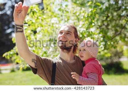 Young bearded hipster father with his cute little daughter taking selfie outdoors