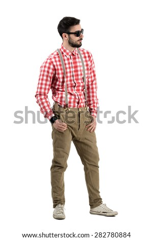 Young bearded hipster with thumbs in pockets looking away. Full body length portrait isolated over white background.  - stock photo
