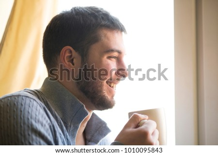 Young bearded holding a ceramic cup. enjoying the smell of his morning coffee or tea, looking out the window