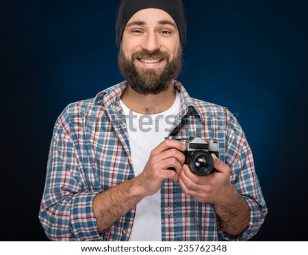 Young bearded man holding old-fashioned camera while standing against blue background.