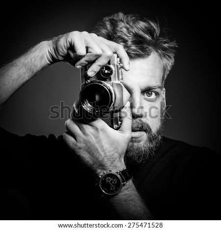 Young bearded man holding retro camera against black background. Confident  photographer shooting at his studio. Black and white photography. Close up. - stock photo