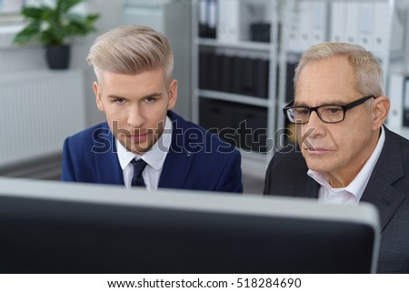 Young bearded man in dark necktie sitting beside boss with computer monitor in foreground and bookshelf in background