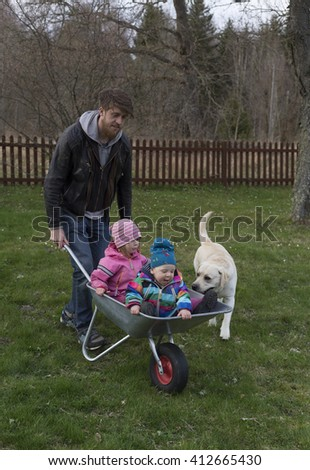 young bearded man is having fun with two small kids outdoors and driving around kids in the gardening cart on the green grass - stock photo