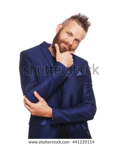 Young bearded man isolated at white background. Portrait of pensive guy with beard thoughtful looking at camera with charming smile. Boy with cool hairstyle, trendy hipster in blue suit. - stock photo