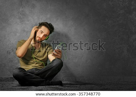 Young bearded man listens music with headphones sitting on grey wall background