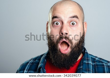 young bearded man looking amazed in to the camera