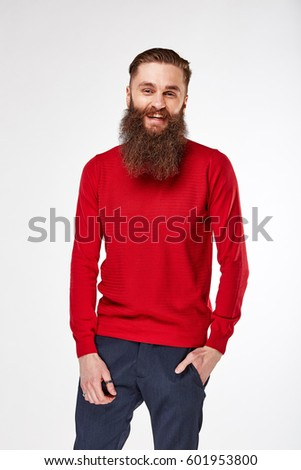 Young bearded man posing in studio in trendy red long-sleeve  shirt with print and blue chinos