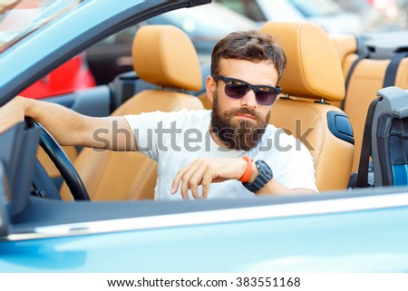 Young bearded man sitting in a convertible - the concept of buying a used car or a rental car - stock photo