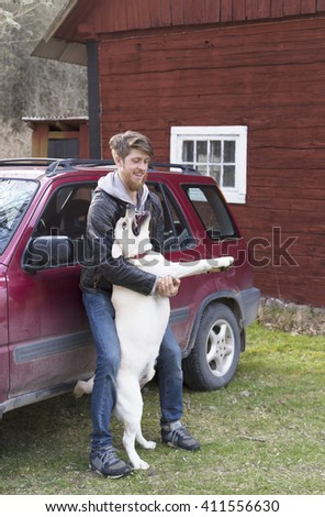 young bearded man standing next to the car and playing or fighting with dog yellow labrador retriever - stock photo