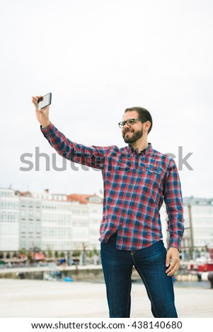 Young bearded man taking a picture with his phone outdoors - stock photo