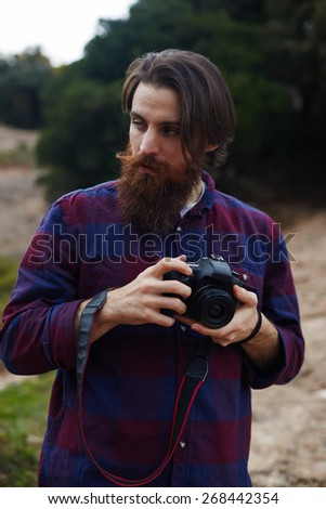 Young bearded man taking photo with his digital camera, handsome hipster tourist checking out the sights in nature landscape, hiker looking out across the nature holding his professional camera - stock photo