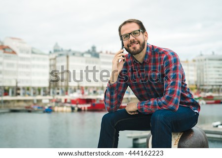 Young bearded man talking on phone while sitting at leisure harbor. Urban maritime vacations lifestyle.