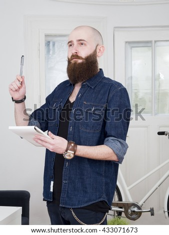 Young bearded man talking on the phone at home during day.