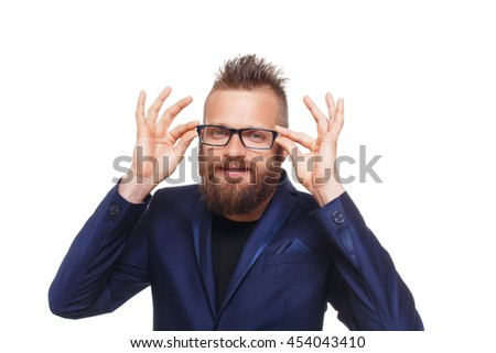 Young bearded man wearing glasses isolated at white background. Portrait of a confident stylish guy in eyeglasses looking at camera. Boy style, trendy hipster with cool hairstyle in blue suit. - stock photo