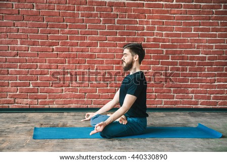 Young bearded man with closed eyes wearing black T-shirt and blue trousers doing yoga position on blue matt at wall background, lotus asana, padmasana, copy space, portrait. - stock photo