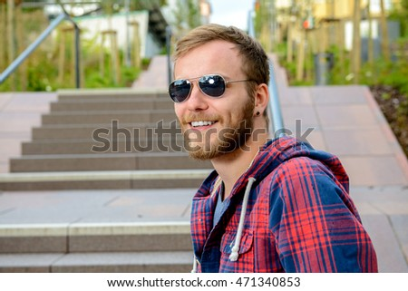 young bearded man with sunglasses in checkered shirt standing on stairs