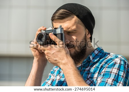 Young bearded man with vintage camera is making a picture. - stock photo