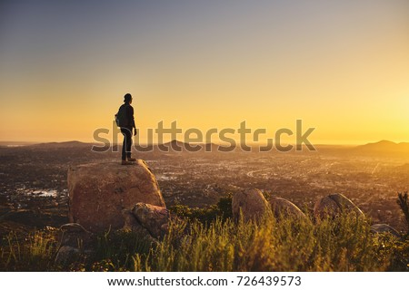young bearded millennial man hiking on top of hill in california over looking san diego at sunset