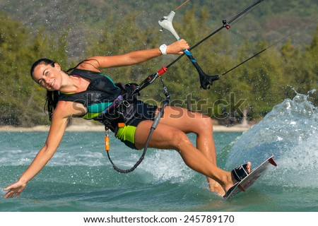 young beautifil girl - kiter riding in the clear waves of the Indian Ocean on the island of Mauritius. Kiting on a background of waves in the spray of ocean - stock photo