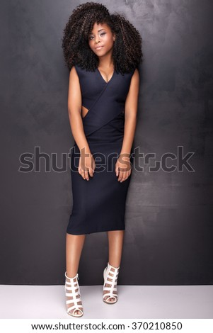 Young beautiful african american girl posing in elegant dress, looking at camera. Girl with afro. Studio shot. - stock photo