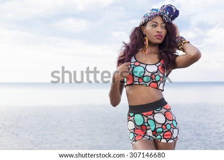 Young beautiful African American girl relaxing at the beach. - stock photo
