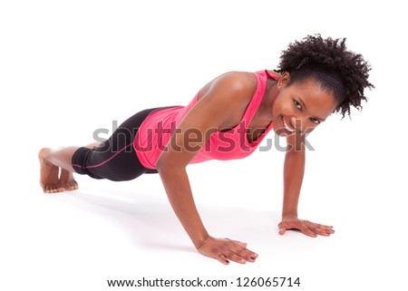Young beautiful african fitness woman doing push up exercises on floor,isolated on white background - stock photo